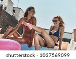 enjoying hot day. two beautiful ... | Shutterstock . vector #1037569099