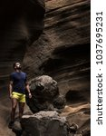 Small photo of Handsome man on yellow shorts stands on rock on scenic sandstone canyon in Gran Canaria, Spain. Hipster with adventure spirit looking up on brown smooth wall passageway corridor in Canary Islands
