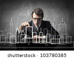 Young businessman putting a skyscraper in the project of a city - stock photo