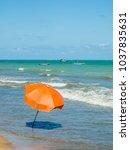 orange beach umbrella near the...   Shutterstock . vector #1037835631