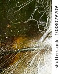 Small photo of Thin cracked ice covers green and yellow murky depths