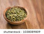 green pumkin seeds in bowl on... | Shutterstock . vector #1038089809