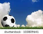 Football in green grass with cloud background - stock photo