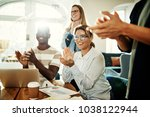 Small photo of Positive group of diverse business colleagues clapping together during a meeting while sitting in a modern office
