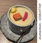 Small photo of Steamed eggs in a tea cup, a japanese style, an accessary to main dish decorated with yellow ginkgo nut, pink fish cake and crab stick on smooth, healthy food.