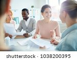 Small photo of Happy young manager or accountant looking at her colleague with smile during conversation