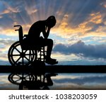 silhouette of a sad disabled... | Shutterstock . vector #1038203059