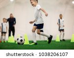 happy boy in uniform kicking... | Shutterstock . vector #1038206107