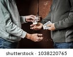 Small photo of Hand of addict man with money buying dose of cocaine or heroine. Drug abuse and traffic concept