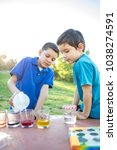 brothers coloring easter eggs | Shutterstock . vector #1038274591