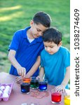 brothers coloring easter eggs | Shutterstock . vector #1038274609