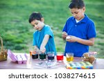brothers coloring easter eggs | Shutterstock . vector #1038274615