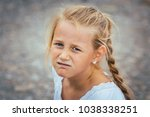grumpy little girl looking into ... | Shutterstock . vector #1038338251