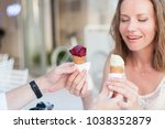 Small photo of Couple of travelers are enjoying and holding ice cream in cones in their hands. Bride has wedding ring. Lovers have dating in sea resort during romantic honeymoon vacation at sunset outdoors.