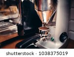 Small photo of Industrial coffee milling machinery pouring fresh coffee into tamper roaster