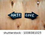 Small photo of Two arrows with words hate and love on rustic wooden table