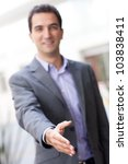 Business man with hand extended to handshake - stock photo