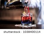 a red cocktail being poured... | Shutterstock . vector #1038400114