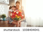 Small photo of happy mother's day! child daughter congratulates mother and gives a bouquet of flowers to tulips