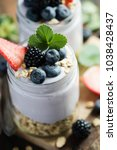 yogurt and granola with berries ... | Shutterstock . vector #1038428437