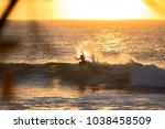 surfer riding into the sunset.  | Shutterstock . vector #1038458509