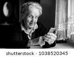 elderly woman typing on a... | Shutterstock . vector #1038520345