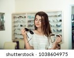Small photo of Which one is better fit me. Portrait of cheerful hesitating woman in optician store, making decision, holding stylish sunglasses, choosing what she should buy. Great discounts for buying two pairs