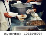 feeding the poor to hands of a...   Shutterstock . vector #1038645034