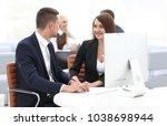 employees sitting behind a desk ... | Shutterstock . vector #1038698944