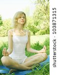 Woman meditating on nature in the lotus position - stock photo