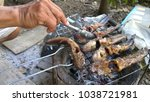 hand with grilled catfish | Shutterstock . vector #1038721981