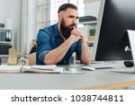 Small photo of Businessman engrossed in his work sitting at a table in a spacious office concentrating on read the screen on his desktop monitor