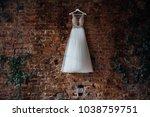 beautiful bridal wedding dress hanging on a hanger on a brick wall in a loft studio. Nobody
