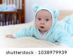 baby on the bed in a bear suit | Shutterstock . vector #1038979939