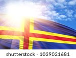 Small photo of flag of Aland against the blue sky with sun rays