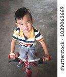 asian little boy playing bike   Shutterstock . vector #1039063669