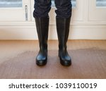 person wearing rubber boots on... | Shutterstock . vector #1039110019