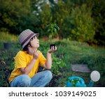 boy in the garden admires the... | Shutterstock . vector #1039149025