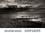 Dark storm clouds gathering over a rocky beach near Homer, Alaska overlooking the Kachemak Bay in black and white. - stock photo