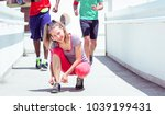 female runner tying up sports... | Shutterstock . vector #1039199431