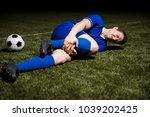 football player lying down on... | Shutterstock . vector #1039202425