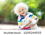 Small photo of Child playing with white rabbit. Little boy feeding and petting white bunny. Easter celebration. Egg hunt with kid and pet animal. Children and animals. Kids take care of pets. Spring Easter garden.