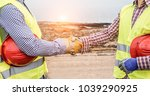 Small photo of Builders on wind farm and photovoltaic plant site making a deal - Happy workers are satisfied of their plan - Dealing, real estate, engineer, industrial and building houses concept