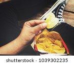 woman eating potato chip   Shutterstock . vector #1039302235