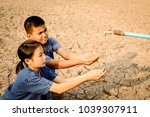Small photo of Sad kids sitting on cracked earth open metal water old faucet on hot and dry empty land. Affected of global warming made climate change. Water shortage and drought concept.