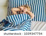 the cute boy woke up in his bed.... | Shutterstock . vector #1039347754