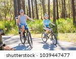 family on a bike ride together... | Shutterstock . vector #1039447477