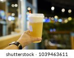hand holding a plastic glass of ... | Shutterstock . vector #1039463611