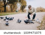 Man feeding pigeons in the old town. Pensioner.