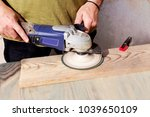 Small photo of Men's hands grind the board with an eccentric grinding machine close-up